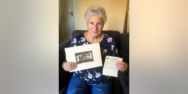 Christine Spall, with the letter and family photograph. (Credit: SWNS)