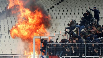 European soccer fans left bloodied after violent rivals throw petrol bombs and flares into the stands