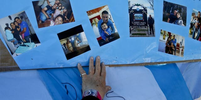 A woman touches a poster, overlaid with snapshots of Celso Oscar Vallejo, one of the crew members of the missing ARA San Juan, that hangs on a fence enclosing the Mar del Plata Naval Base, in Argentina, Thursday, Nov. 23, 2017.