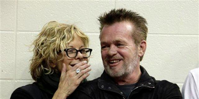 Actress Meg Ryan, left, talks with performer John Mellencamp during the second half of an NCAA college basketball game between Indiana and Ohio State, Saturday, Dec. 31, 2011, in Bloomington, Ind. Indiana won 74-70.