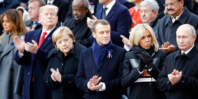 U.S President Donald Trump, second left, and first lady Melania Trump, left, German Chancellor Angela Merkel, third left, French President Emmanuel Macron and his wife Brigitte, Russian President Vladimir Putin, right, applaud after ceremonies at the Arc de Triomphe Sunday, Nov. 11, 2018 in Paris. Over 60 heads of state and government were taking part in a solemn ceremony at the Tomb of the Unknown Soldier, the mute and powerful symbol of sacrifice to the millions who died from 1914-18. (AP Photo/Francois Mori, Pool)