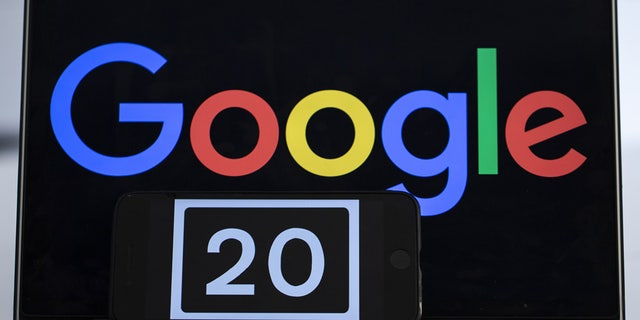 A screen of a mobile phone shows the number of '20' referring to the 20th anniversary of Google.