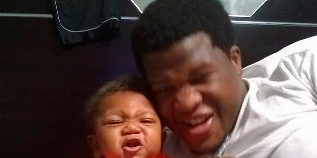 """This photo provided by Avontea Boose shows her baby Tristan Roberson and the boy's father Jemel Roberson. A police officer fatally shot Jemel Roberson, an armed security guard who was wearing a hat with """"security"""" emblazoned across the front and holding a man down following a shooting inside the suburban Chicago bar where the guard worked, an attorney for the guard's family said Monday, Nov. 12, 2018, after filing a federal lawsuit. (Avontea Boose via AP)"""