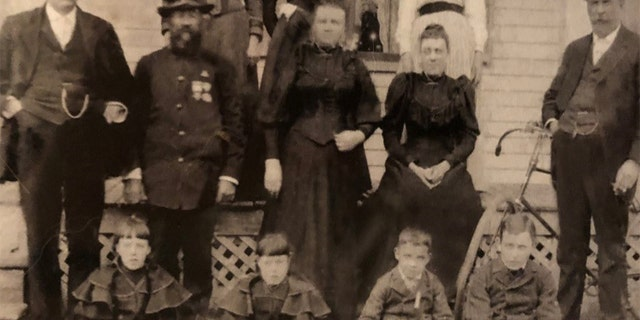 Maker would often write home to his family during World War I. He is pictured here as a young boy, on the far right of the bottom row. To his side, from right to left, are his stepsister Harriet, sister Eva and brother Clifford (Kip). His uncle Edward, wearing a Union Army uniform, is second from the left in the middle row, next to Edward's brother, Andrew. Both of those men fought for 19th Maine Regiment during the Civil War. Maker's father, Winfield, is standing in front of the bicycle on the far right.