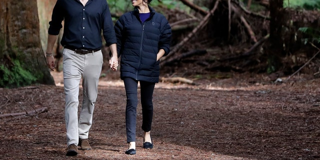 Britain's Prince Harry and Meghan, Duchess of Sussex walk through a Redwoods forest in Rotorua, New Zealand, Wednesday, Oct. 31, 2018. Prince Harry and his wife Meghan are on the final day of their 16-day tour of Australia, New Zealand and the South Pacific.