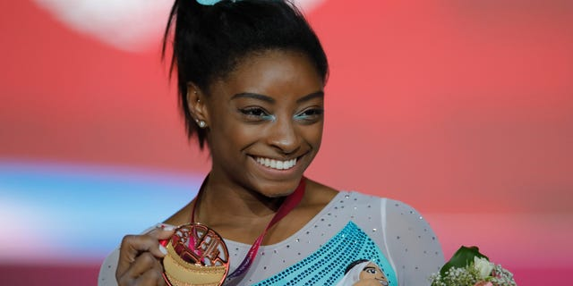 Gold medallist and four-times All-Around world champion Simone Biles poses on the podium after the Women's All-Around Final of the Gymnastics World Championships at the Aspire Dome in Doha, Qatar, Nov. 1, 2018. (AP Photo/Vadim Ghirda)