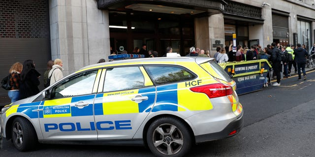 Police officers and security watch as people re-enter a building after a stabbing incident in central London, Friday, Nov. 2, 2018. British police say two people have been stabbed and a man has been arrested at an address in central London that is home to the offices of Sony Music. (AP Photo/Alastair Grant)
