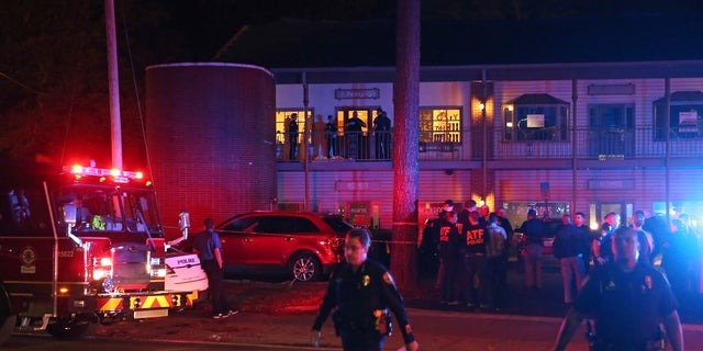 Police investigators work the scene of a shooting, Friday, Nov. 2, 2018, in Tallahassee, Fla. A shooter killed one person and critically wounded four others at a yoga studio in Florida's capital before killing himself Friday, officials said. (AP Photo/Steve Cannon)