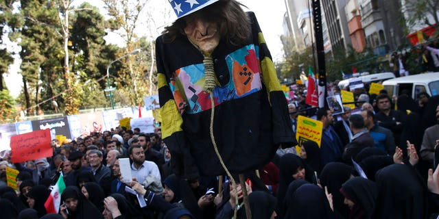 """FILE: An effigy of U.S. government icon """"Uncle Sam"""" is held up by demonstrators during a rally in front of the former U.S. Embassy in Tehran, Iran."""