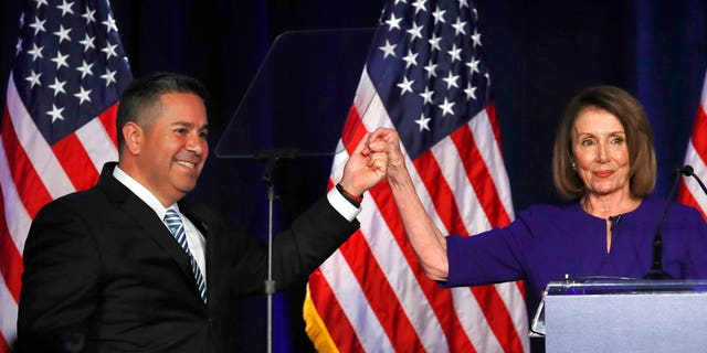 Democratic Congressional Campaign Committee Chairman Ben Ray Luján and House Democratic Leader Nancy Pelosi of California gesture after speaking to party volunteers and supporters Tuesday.