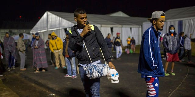 A Central American migrant prepares to leave the temporary shelter in the Jesus Martinez stadium, in Mexico City, Friday, Nov. 9, 2018.