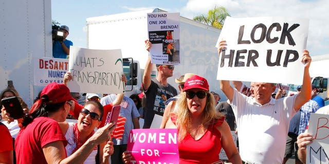 A crowd protests outside the Broward County Supervisor of Elections office Friday, Nov. 9, 2018, in Lauderhill, Fla. Florida is once again at the center of election controversy, but this year there are no hanging chads or butterfly ballots like in 2000. And no angry mobs in suits, at least not yet. (AP Photo/Joe Skipper)