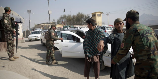In this Oct. 26, 2018 photo, Afghan National Security Forces search passengers and their vehicles at a checkpoint in Kabul, Afghanistan. (AP Photo/Massoud Hossaini)