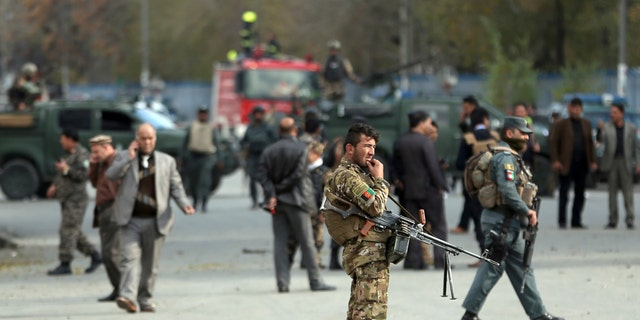 Security forces inspect the site of a deadly blast near a demonstration by hundreds of minority Shiites, in the center of Kabul, Afghanistan, Monday, Nov. 12, 2018. Afghan officials confirmed several people were killed in the explosion near a high school and about 500 meters (yards) from where people gathered to denounce Taliban attacks in Jaghuri and Malistan districts of eastern Ghazni province.