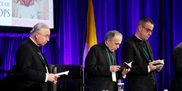 Cardinal Daniel DiNardo of the Archdiocese of Galveston-Houston, center, president of the United States Conference of Catholic Bishops, participates in a morning prayer alongside Jose Gomez, archbishop of Los Angeles and conference vice president, at left, and Rev. J. Brian Bransfield, conference general secretary, at the USCCB's annual fall meeting, Tuesday, Nov. 13, 2018, in Baltimore. (AP Photo/Patrick Semansky)