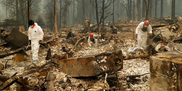 Search and rescue workers search for human remains at a trailer park burned by the Camp Fire, Tuesday, Nov. 13, 2018, in Paradise, California.