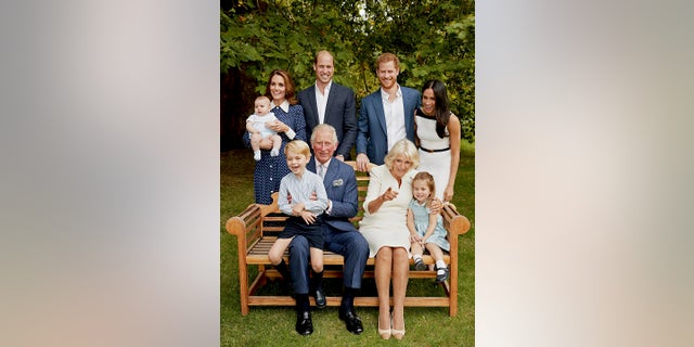 In this handout image provided by Clarence House and taken on Sept. 5, 2018, Britain's Prince Charles poses for an official portrait to mark his 70th Birthday in the gardens of Clarence House, with Camilla, Duchess of Cornwall, Prince William, Kate, Duchess of Cambridge, Prince George, Princess Charlotte, Prince Louis, Prince Harry and Meghan, Duchess of Sussex, in London, England.