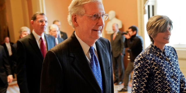 Senate Majority Leader Mitch McConnell, R-Ky., center, walks out to speak to media after a meeting in his office at the Capitol in Washington.