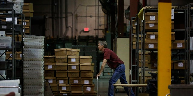 An employee at the Palm Beach County Supervisor of Elections office pushes a pallet of ballot boxes during a recount on Wednesday, Nov. 14, 2018, in West Palm Beach, Fla. (AP Photo/Brynn Anderson)