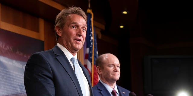 Sen. Jeff Flake, R-Ariz., left, and Sen. Chris Coons, D-Del., speak to reporters about their effort to bring up legislation to protect Special Counsel Robert Mueller.