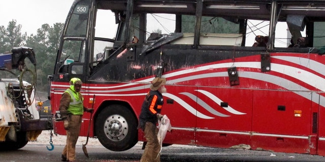 Workers clear debris from the scene of a bus crash that killed at least two people and injured dozens on Wednesday, Nov. 14, 2018, in Byhalia, Miss.