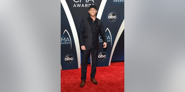 Cole Swindell wears a navy and gray suit to the CMA Awards carpet.