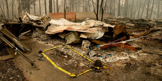 Tape marks a spot where sheriff's deputies recovered the body of a Camp Fire victim on Wednesday, Nov. 14, 2018, in Paradise, California.
