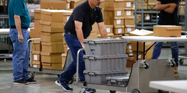 Employees bring out boxes of ballots before resuming a recount at the Palm Beach County Supervisor Of Elections office, Thursday, Nov. 15, 2018, in West Palm Beach, Fla. (AP Photo/Wilfredo Lee)