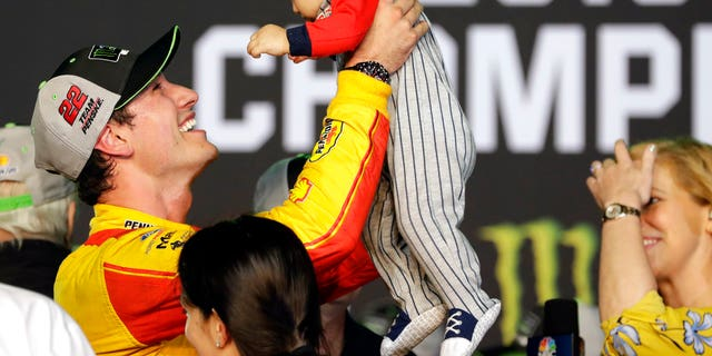 Joey Logano holds his son Hudson after winning the NASCAR Cup Series Championship auto race at the Homestead-Miami Speedway, Sunday, Nov. 18, 2018, in Homestead, Florida.
