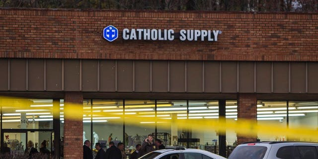 Authorities investigate the scene at a Catholic Supply store where a gunman went into the religious supply store, sexually assaulted at least one woman and shot a woman in the head.