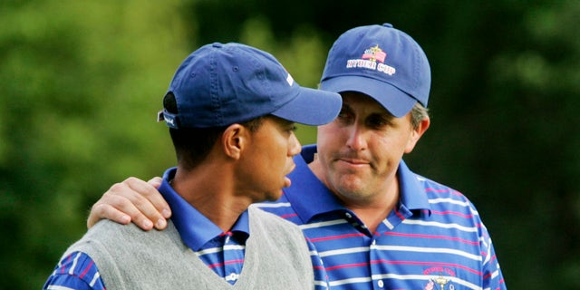 In this Sept. 17, 2004, file photo, U.S. team player Phil Mickelson puts his arm around partner Tiger Woods as they walk off the 18th green after they lost to Europeans Darren Clarke and Lee Westwood on the final hole of their foursomes match at the 35th Ryder Cup at Oakland Hills Country Club in Bloomfield Township, Mich. They play a high-stakes exhibition Friday in Las Vegas in golf's first venture using pay-per-view.