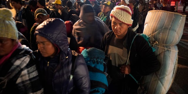 Central American migrants wait to access to the shelter in Tijuana, Mexico, Tuesday, Nov. 20, 2018. At least 3,000 migrants have arrived in Tijuana and the federal government estimates the number of migrants could grow to 10,000 in the coming weeks and months. (AP Photo/Ramon Espinosa)