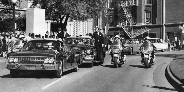 FILE - In this Nov. 22, 1963, file photo, seen through the foreground convertible's windshield, President John F. Kennedy's hand reaches toward his head within seconds of being fatally shot as first lady Jacqueline Kennedy holds his forearm as the motorcade proceeds along Elm Street past the Texas School Book Depository in Dallas.