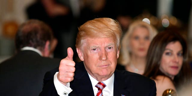 President Donald Trump gives a thumbs-up as he has Thanksgiving Day dinner at his Mar-a-Lago estate in Palm Beach, Fla., Thursday