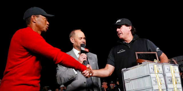 Tiger Woods, left, shakes hands after losing a golf match to Phil Mickelson, right, at Shadow Creek golf course, Friday, Nov. 23, 2018, in Las Vegas.
