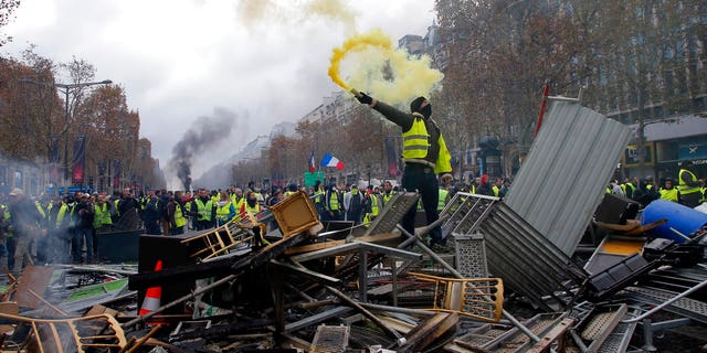 A demonstrator holds a flare on a barricade on the Champs-Elysees avenue during a demonstration against the rising of the fuel taxes, Saturday, Nov. 24, 2018 in Paris.