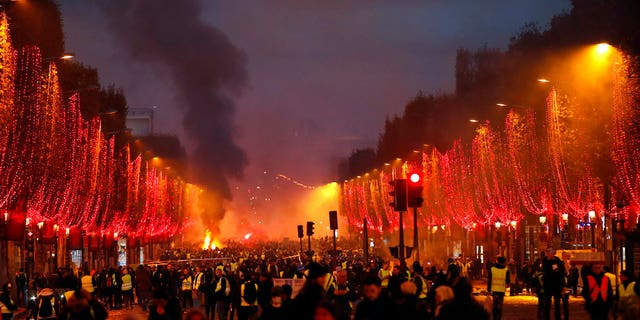 Plumes of smoke are seen the Champs-Elysees avenue decorated with the Christmas lightings during a protest against tax Saturday