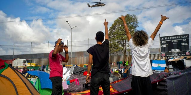 Migrants wave at U.S. border control helicopters flying near the Benito Juarez Sports Center serving as a temporary shelter for Central American migrants, in Tijuana, Mexico, Saturday, Nov. 24, 2018. The mayor of Tijuana has declared a humanitarian crisis in his border city and says that he has asked the United Nations for aid to deal with the approximately 5,000 Central American migrants who have arrived in the city. (AP Photo/Ramon Espinosa)