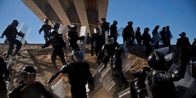 Mexican police run as they try to keep migrants from getting past the Chaparral border crossing in Tijuana, Mexico near San Ysidro, California.