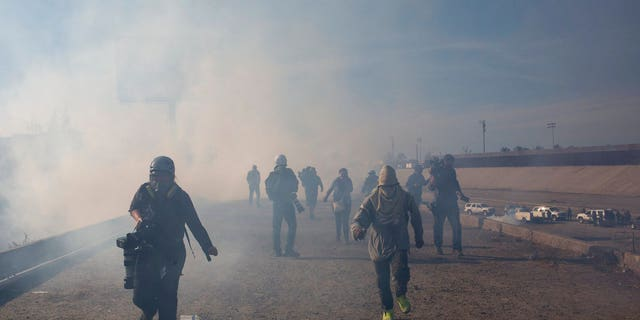 Migrants run from tear gas launched by U.S. agents, amid photojournalists covering the Mexico-U.S. border, after a group of migrants got past Mexican police at the Chaparral crossing in Tijuana, Mexico, Sunday, Nov. 25.