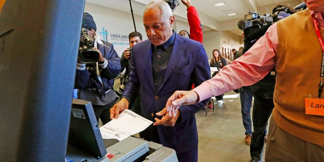 Democrat Mike Espy, left feeds his ballot into the submission machine, as directed by poll manager Larry Greer, Tuesday, Nov. 27, 2018 in Ridgeland, Miss. Mississippi voters are deciding the last U.S. Senate race of the midterms, choosing between Espy and Republican Sen. Cindy Hyde-Smith. (AP Photo/Rogelio V. Solis)