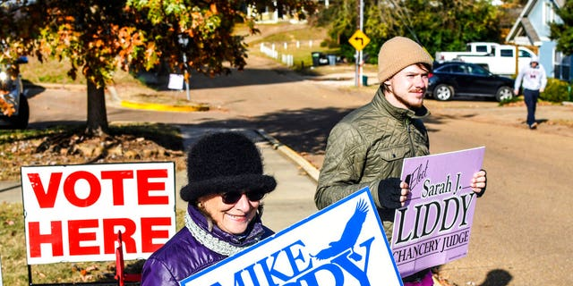 Susan Fino, left, holds a sign for U.S. Senate candidate Mike Espy and Logan Liddy holds one for Susan Liddy, a candidate for judge in the Chancery Court, District 18, Place 1 race at the Oxford Community Center in Oxford, Miss. on Tuesday, November 27, 2018. Mississippians are casting their ballots in runoff elections, including a U.S. Senate race pitting Republican Cindy Hyde-Smith against Democrat Mike Espy. (Bruce Newman/The Oxford Eagle via AP)