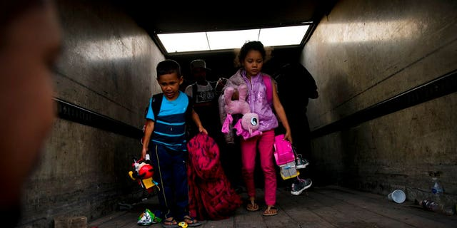 Migrant children arrive to Tijuana after traveling in a truck from Mexicali, part of the migrant caravan, in Mexico, Tuesday, Nov. 27, 2018. Tension continued Tuesday as residents in the Mexican border city of Tijuana closed down a school next to a sports complex where more than 5,000 Central American migrants have been camped out for two weeks.