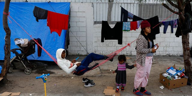 A migrant family camps on the street outside of an overflowing sports complex where more than 5,000 Central Americans are sheltering, in Tijuana, Mexico, Wednesday, Nov. 28, 2018.