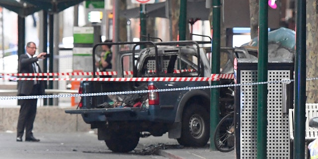 A burnt out vehicle is seen on Bourke Street in Melbourne, Friday, Nov. 9, 2018.