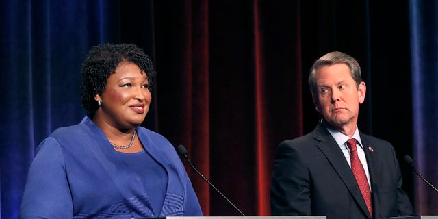 FILE - Democratic gubernatorial candidate for Georgia Stacey Abrams, left, speaks as her Republican opponent Secretary of State Brian Kemp looks on during a debate in Atlanta.