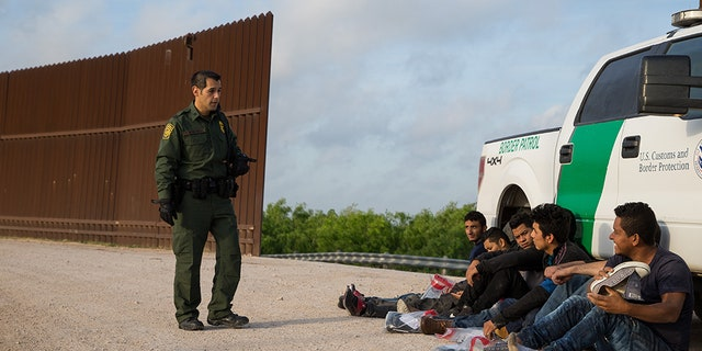 A Border Patrol agent near McAllen, Texas, apprehends illegal immigrants last March, shortly after they crossed the border from Mexico.