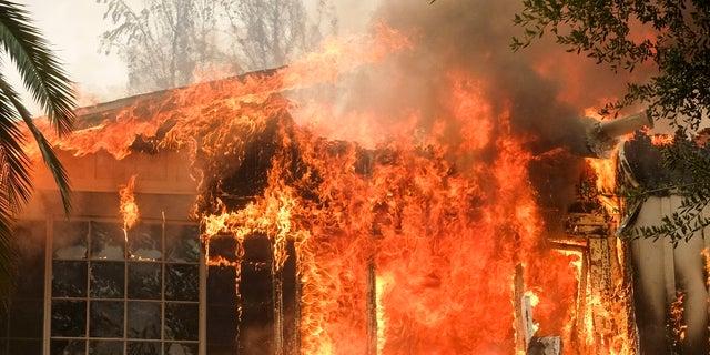 The Woolsey Fire burns a home near Malibu Lake in Malibu, Calif.