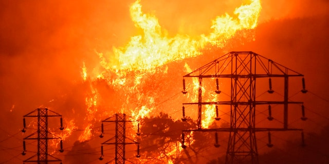 FILE - Flames burn near power lines in Montecito, Calif., Dec. 16, 2017. (Mike Eliason/Santa Barbara County Fire Department via AP)