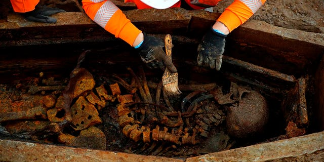 A field archaelogist uses a brush on a skeleton in an open coffin during the excavation of a late 18th to mid 19th century cemetery under St James Gardens near Euston train station in London on November 1, 2018 as part of the HS2 high-speed rail project. (Credit: ADRIAN DENNIS/AFP/Getty Images)